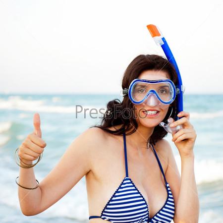 Девушка с мокрой кожей и трубкой стоит на пляже после купания в чистом Средиземное море