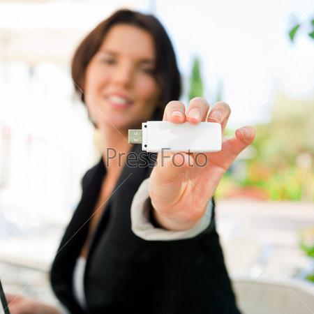 Молодая деловая женщина пользуется беспроводным подключением к интернету с модемом 3g за ланчем в летнем кафе