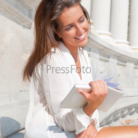 Красивая темноволосая девушка в белой блузке читает книгу на фоне здания музея или галереи эпохи Возрождения