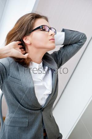 Фотография на тему Красивая деловая женщина потягивается во время работы на компьютере в офисе