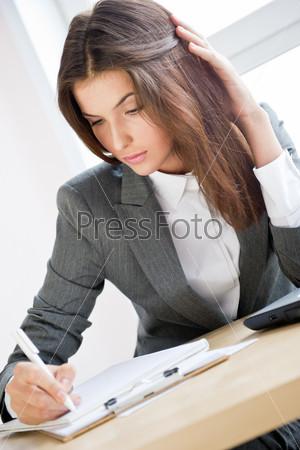 Красивая деловая женщина подписывает документы в офисе