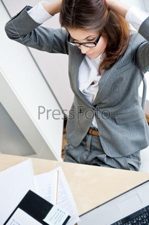 Красивая деловая женщина потягивается во время работы на компьютере в офисе
