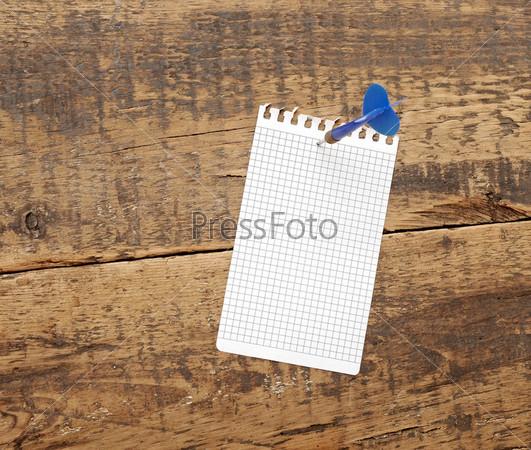 Дротик с листком бумаги на доске