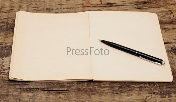 Блокнот и ручка на деревянном столе