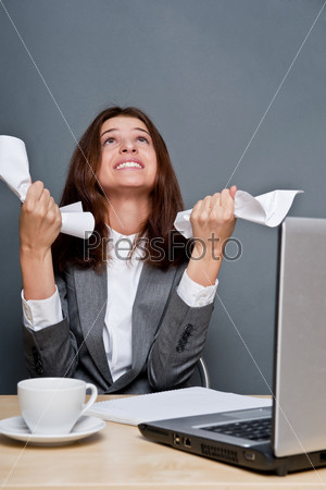 Расстроенная деловая женщина держит в руках смятую бумагу, сидя в офисе