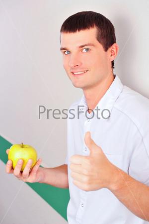 Счастливый стоматолог стоит с зеленым яблоком у стены стоматологической клиники