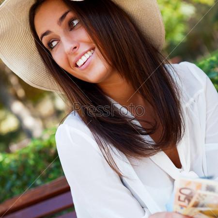 Стильная симпатичная девушка в соломенной шляпе и белой блузке сидит в парке с деньгами в руках и мечтает, глядя на небо