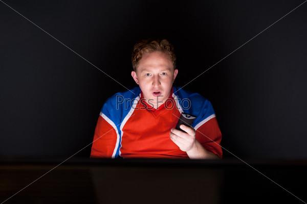 Болельщик смотрит телевизионную трансляция матча своей любимой команды