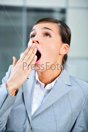 Деловая женщина зевает в офисе