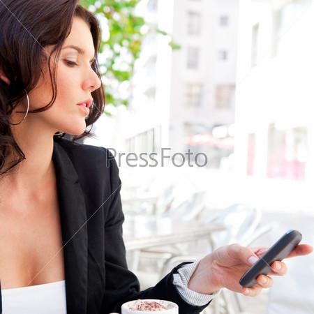 Портрет красивой молодой бизнес-леди, сидящей в летнем кафе за чашкой кофе в обеденное время с мобильным телефоном