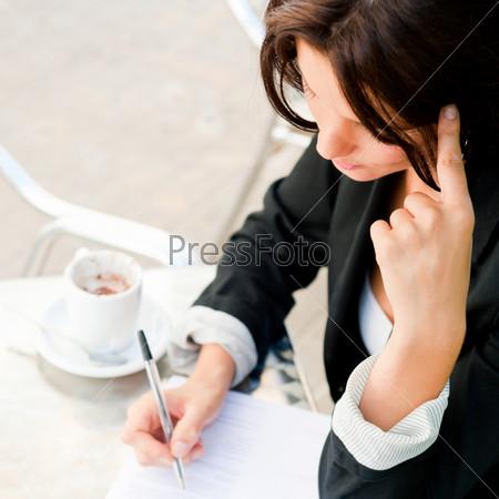 Портрет бизнес-леди, подписывающей документ в летнем кафе в обеденное время