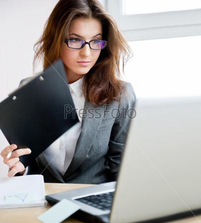 Чрезвычайно занятая красивая деловая женщина работает в офисе