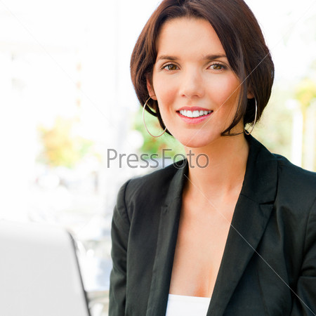 Портрет молодой бизнес-леди с ноутбуком в летнем кафе