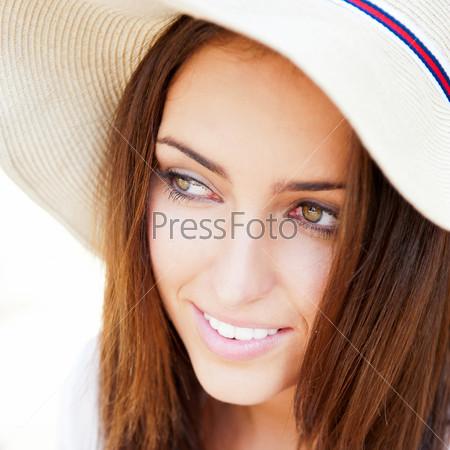 Молодая элегантная женщина в соломенной шляпе отдыхает и мечтает в парке