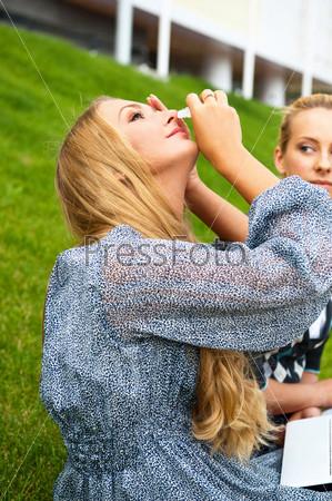 Фотография на тему Две женщины в городском парке сидят на зеленой траве. Одна из них закапывает в глаза, так как устала от чтения