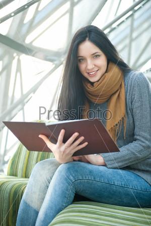 Привлекательная девушка держит меню в кафе и смотрит в камеру