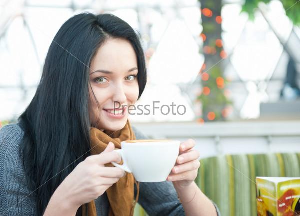 Привлекательная девушка пьет кофе в кафе