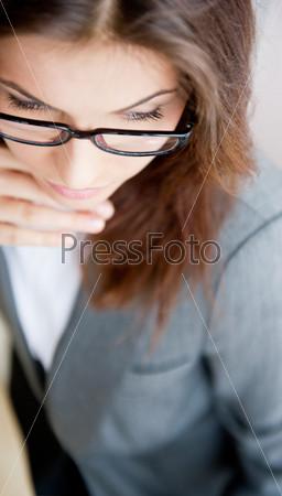 Красивая деловая женщина в очках сидит за столом и сморит в сторону