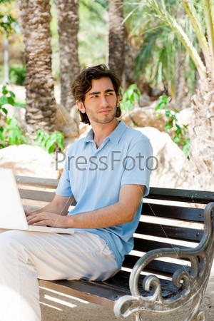 Портрет молодого человека с ноутбуком в парке