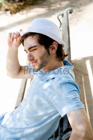 Фотография на тему Портрет молодого человека, сидящего на солнце на скамье в парке