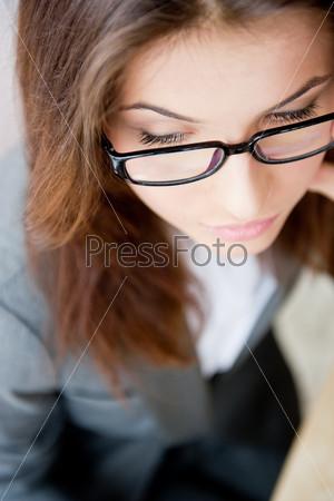 Фотография на тему Красивая деловая женщина в очках сидит за столом и сморит в сторону