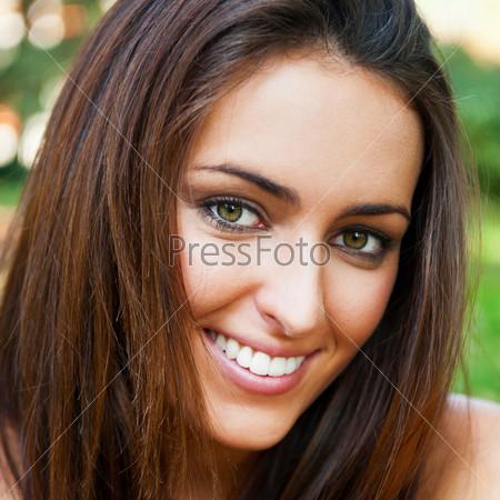 Симпатичная девушка сидит на траве в лесу, глядя в камеру