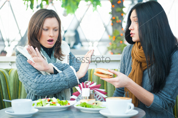 Привлекательные девушки пьют чай, болтая за обедом в кафе