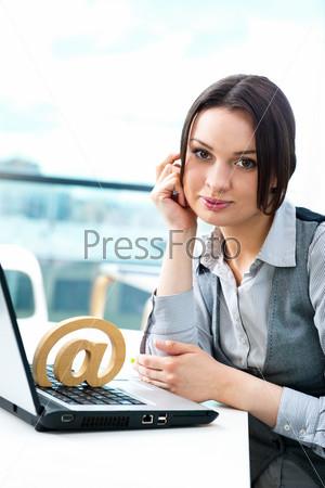 Веселая деловая женщина сидит за столом с символом электронной почты на клавиатуре и думает о любви