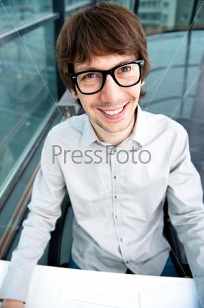 Портрет привлекательного стильного молодого человека, работающего в офисе и глядящего в камеру