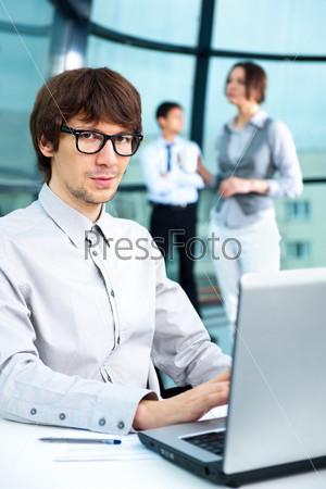 Фотография на тему Портрет привлекательного стильного молодого человека, работающего на компьютере и глядящего в камеру