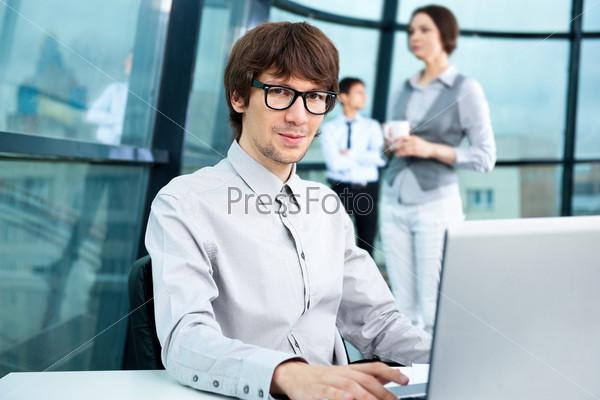 Портрет привлекательного стильного молодого человека, работающего на компьютере и глядящего в камеру