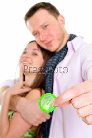 Безопасный секс. Обнимающаяся влюбленная пара с презервативом в руках, изолированная на белом фоне