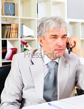 Портрет пожилого делового человека, говорящего по телефону в офисе