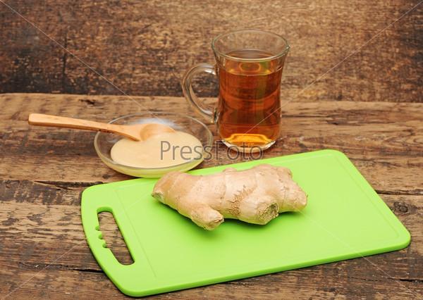 Чашка чая, имбирь и мед на деревянном кухонном столе