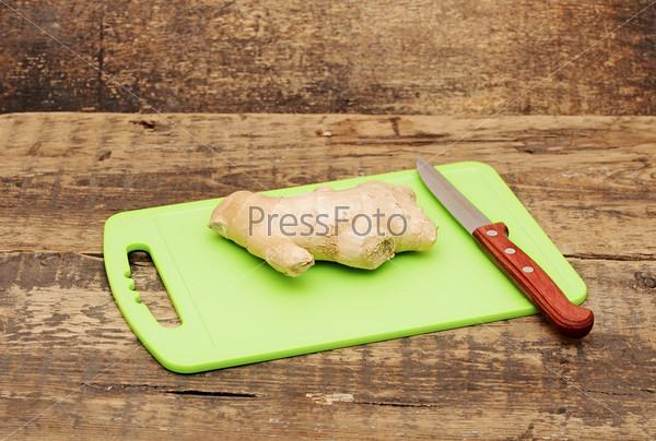 Фотография на тему Корень имбиря и нож на кухонной доске
