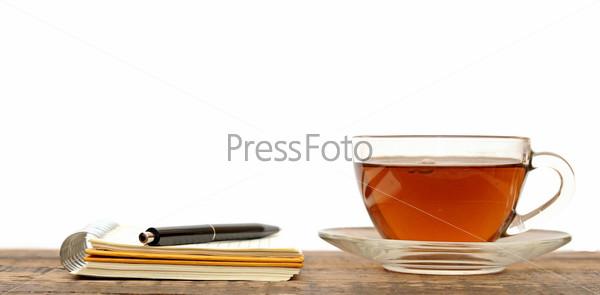 Блокнот с ручкой и чашка чая на деревянном столе