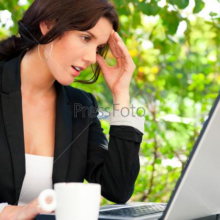 Портрет бизнес-леди с ноутбуком в летнем кафе