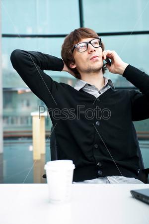 Деловой мужчина в офисе разговаривает по мобильному телефону