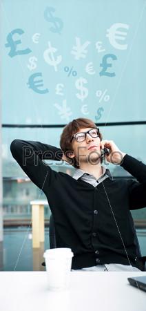 Фотография на тему Деловой мужчина в офисе разговаривает по мобильному телефону на фоне большого окна с символами различных валют