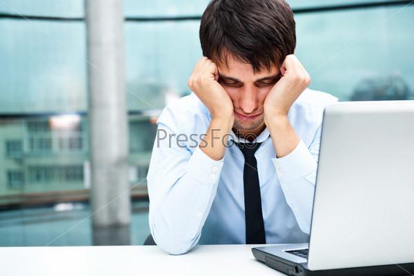 Уставший бизнесмен с ноутбуком на рабочем месте