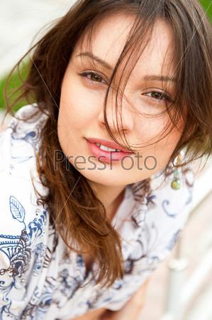 Симпатичная улыбающаяся девушка отдыхает на траве