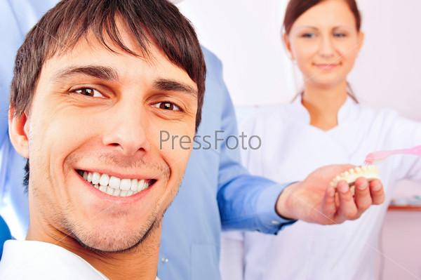 Счастливый улыбающийся пациент, стоматолог и медсестра в кабинете