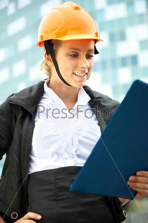 Молодой архитектор в защитной каске на фоне здания