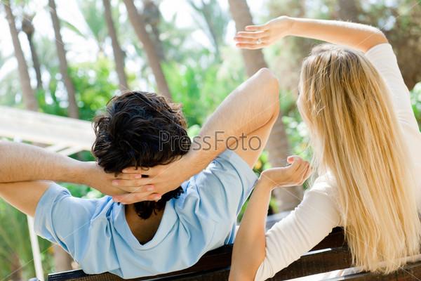 Красивая пара мечтает о чем-то на скамье в летнем парке