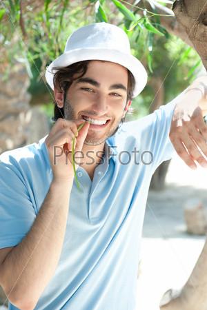 Молодой человек в шляпе и повседневной одежде стоит, прислонившись к пальмовому стволу в летнем парке