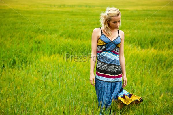 Беззаботная очаровательная женщина в ярком платье стоит в летнем поле на закате
