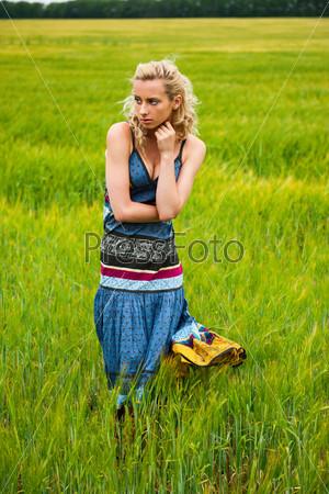 Фотография на тему Беззаботная очаровательная женщина в ярком платье стоит в летнем поле на закате