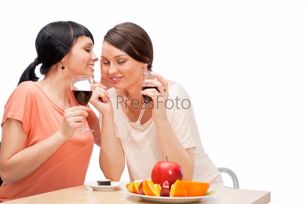 Веселые женщины едят фрукты и пьют красное вино