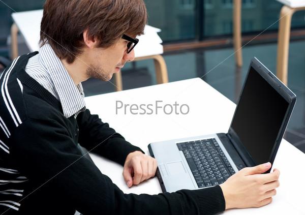 Молодой человек перед ноутбуком в кабинете