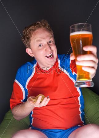 Фотография на тему Болельщик смотрит телевизионную трансляцию матча своей любимой команды и пьет пиво